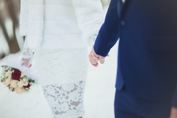 The bride and groom are gently holding hands at the wedding, close-up in the winter