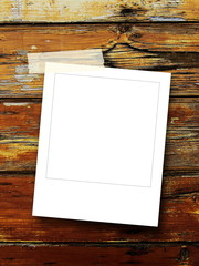 Single blank square frame on brown wooden boards with adhesive tape