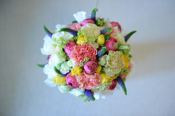 Colorful mixed wedding bouquet positioned on a white cushion  viewed from above