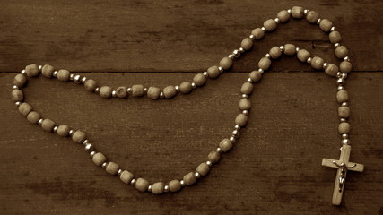 A rosary with beads on wooden textured background. Sepia
