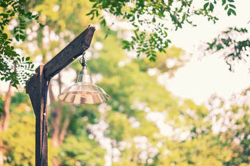 simple basic lamp on old rustic wooden lampost against blurred trees and sky background