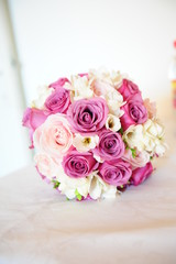Wedding bouquet with different roses with pink hues positioned on a white cushion
