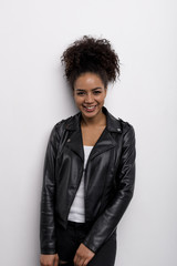 Trendy woman wearing leather jacket at white wall