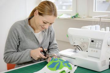 Frau mit Nähmaschine schneidet Stoff für DIY mit Schere