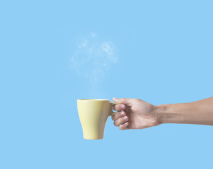 hand holding green coffee cup isolated on blue background.