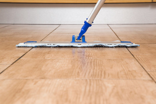 Tiles floor washing with mop in the kitchen. Regular clean up. Maid cleans house.