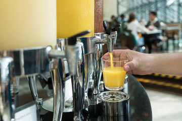 Hand holding glass refill orange juice for row of fresh juice at buffet restaurant, Juice buffet self service in morning at hotel.
