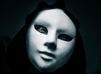 Artistic, monochrome picture of a white carnival mask weared by a woman in darc clothes