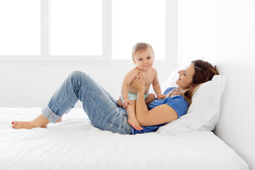 mother lying down on the bed holding her baby on her stomach and smiling