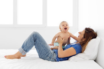 mother and baby laughing together on the bed