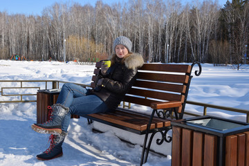The girl sits on a bench in the park and drinks hot tea from a thermos bottle.