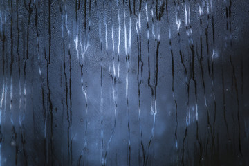Dark blue rainy window with scary pattern of the raindrops paths