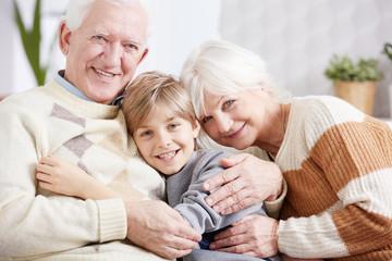 Grandparents embracing their grandson