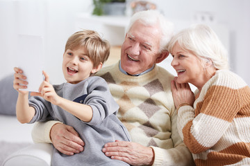 Boy taking selfie with grandparents