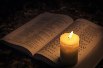 Candle illuminating the bible in the dark