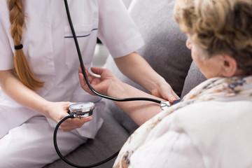 Nurse taking pressure of patient