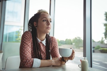 Thoughtful woman having cup of coffee