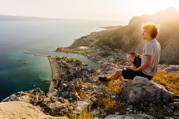 A young guy in a T-shirt and shorts sits high on a rock against the background of the sea and looks out into the distance.