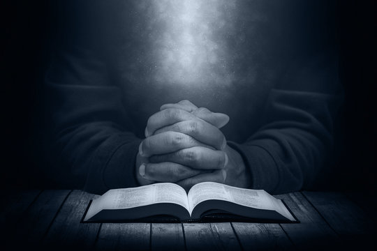 Man praying on a wooden table with an open Bible in the dark.