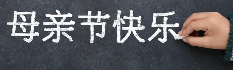 Enfant écrivant bonne fête des mères en chinois à la craie sur une ardoise