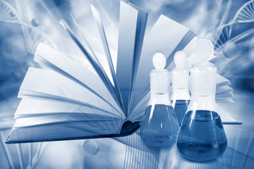 books and laboratory flask on DNA strand background