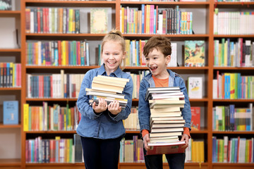 Cute boy and girl  reading book in library
