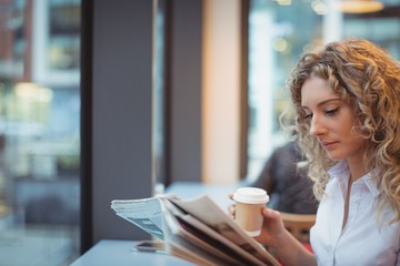 Woman reading newspaper while having coffee