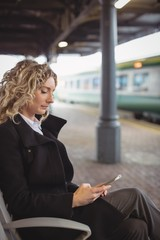 Woman sitting on platform using mobile phone