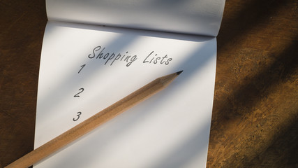 Top view point picture of brown pencil and white blank note page on wooden block under hard light