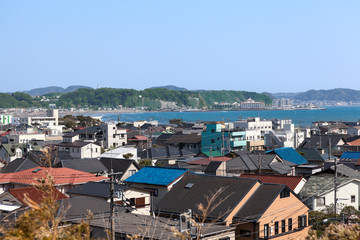 KAMAKURA, JAPAN - CIRCA APR, 2013: Top view at the Kamakura town. Houses with color roofs are on the coastline of Pasific ocean. Kamakura is a small town in Kanagawa Prefecture