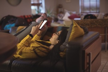 Woman lying and using mobile phone at home