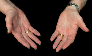 Older lady's hands, palms up on a black background.