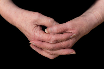 Close up of a female pensioner's hands loosely clasped