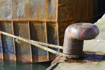 Rusty bollard and mooring rope in the fishing harbor of Lorient, Brittany France
