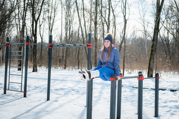 Beautiful young girl doing stretching, fitness on a sports field in winter against a background of deciduous forest. Winter sports concept photo