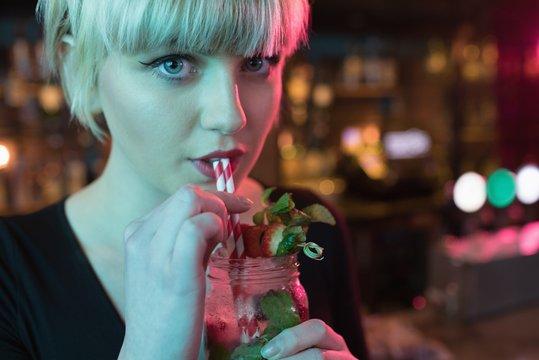 Beautiful woman having cocktail in bar