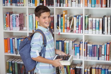 Happy schoolboy selecting books in library