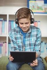 Happy schoolboy using digital tablet