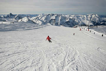 Girl skier making large turns in snowy mountains