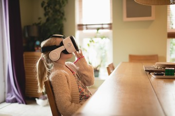 Girl sitting at table and using virtual realty headset