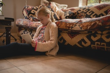 Girl sitting on floor and using digital tablet in living room
