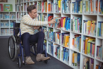 Disabled school teacher selecting book in library