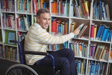 Portrait of disabled school teacher selecting book in library