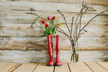 colorful rain boots with spring flowers and willow branches in wooden background