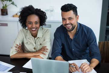 Portrait of smiling two business executives working on laptop
