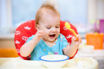 One year old child plays in the kitchen with dishes