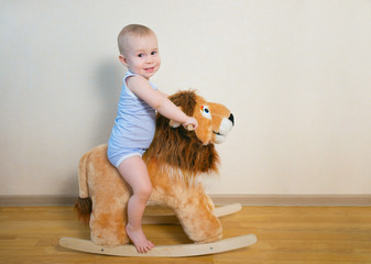 Cute small baby boy riding on the lion toy . Happy child emotions.