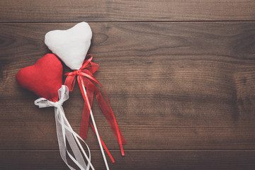 red and white plush heart shapes on sticks over wooden background