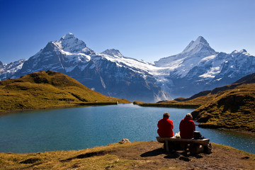 Swiss hikers (red jackets) on a picnic overlooking lake and Wetterhorn mountain. High above Grindelwald.