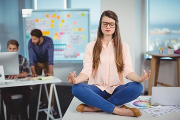 Female graphic designer sitting on table and meditating